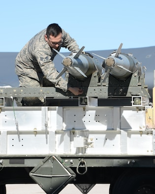 Senior Airman Carlos Del Valle III, a weapons load crew member assigned to the 37th Aircraft Maintenance Unit, retrieves a Mark 82 General Purpose bomb for a load competition at Ellsworth Air Force Base, S.D., March 17, 2017. The loading standardization crew evaluates each competing team on performing safe and reliable weapons loading operations in accordance with B-1 bomber weapons loading technical orders and Air Force instructions. (U.S. Air Force photo by Airman Nicolas Z. Erwin)