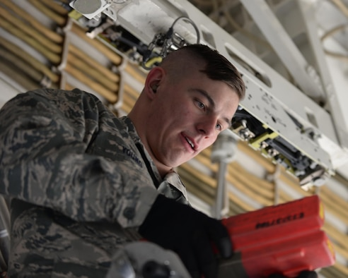 Airman 1st Class Chance Young, a weapons load crew member assigned to the 37th Aircraft Maintenance Unit looks for a tool to assist with the installation of a Mark 82 General Purpose bomb during a load competition at Ellsworth Air Force Base, S.D., March 17, 2017. The armaments of the B-1 bomber must be checked and verified to ensure all weapon systems are operational for B-1 missions. (U.S. Air Force photo by Airman Nicolas Z. Erwin)