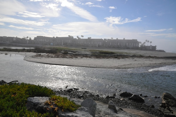 In previous years, sand across the mouth of the San Luis Rey River blocked its connection to the Pacific Ocean,  providing a continuous shoreline. Recent rains have opened the river to the ocean, requiring the contractor to develop a means to span the flowing water in order to replenish the beach to the south.