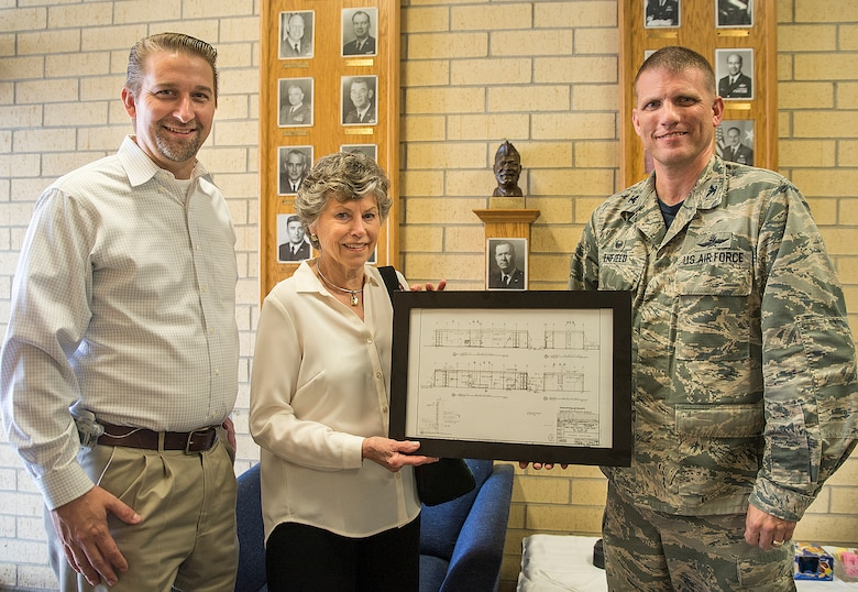 Col. David Enfield, 433rd Mission Support Group commander, presents Peggy Marchbanks and her son Tobin Marchbanks, with a framed copy of the original blueprints of the Marchbanks building March 17, 2017 at Joint Base San Antonio-Lackland, Texas. Peggy Marchbanks  was accompanied by her son Tobin Marchbanks, daughter-inlaw Lorisha Marchbanks, grandson Colin Marchbanks, and sister Nancy Richter. She is the widow of Maj.Gen. Tom E. Marchbanks, Jr. the first chief, Air Force Reserve, and former 433rd Airlift Wing commander. (U.S.  Air Force photo by Benjamin Faske)