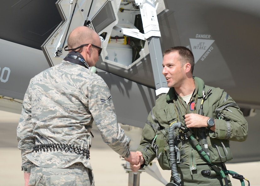 Lt. Col. Matthew Vedder, 63rd Fighter Squadron commander, shakes hands with Airman 1st Class Joshua Cote, 61st Aircraft Maintenance Unit F-35 Lightning II crew chief after landing March 20, 2017, at Luke Air Force Base, Ariz. This is the first F-35 for the 63rd FS and marks the 51st F-35 for Luke. (U.S. Air Force photo by Senior Airman James Hensley)