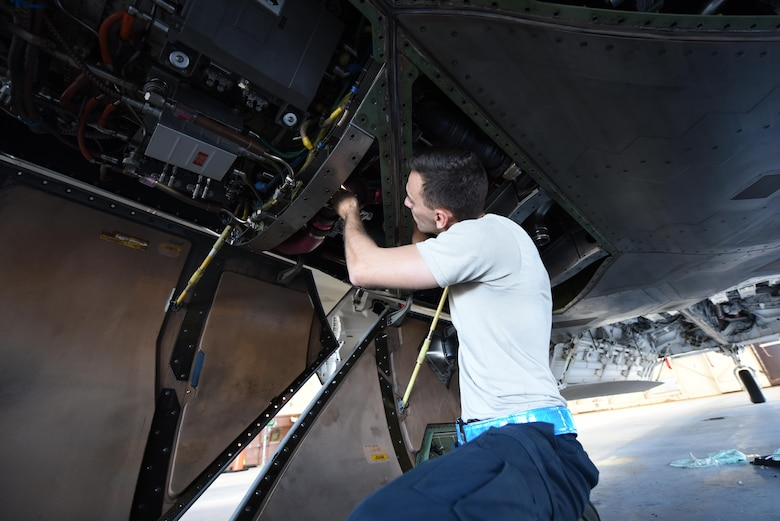 U.S. Air Force Tech. Sgt. Robert Mackle, 325th Aircraft Maintenance Squadron dedicated crew chief, inspects the underbelly of an F-22 Raptor in Hangar 2 at Tyndall Air Force Base, Fla., March 20, 2017. Prior to a sortie, dedicated crew chiefs like Mackle inspect and maintain the aircraft to ensure the F-22's operational readiness. (U.S. Air Force photo by Senior Airman Solomon Cook/Released)