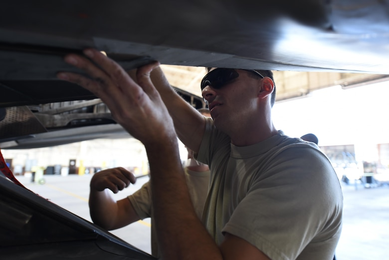 U.S. Air Force Tech. Sgt. Robert Mackle, 325th Aircraft Maintenance Squadron dedicated crew chief, attaches a panel to an F-22 Raptor in Hangar 2 at Tyndall Air Force Base, Fla., March 20, 2017. Throughout the course of a day, dedicated crew chiefs like Mackle inspect and maintain the aircraft of the 95th Fighter Squadron prior to pilots' takeoff for training. (U.S. Air Force photo by Senior Airman Solomon Cook/Released)