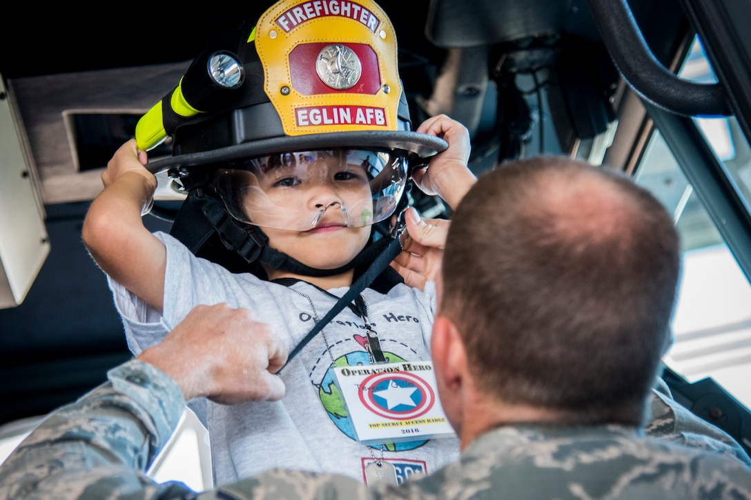 An airman helps a child with his fire hat