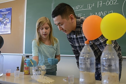 Katelyn Diamond, 10, and Army 2nd Lt. Roger Tran, 103rd Civil Support Team nuclear medical science officer, test the acidity levels of lemon juice during the Spring Break Science Program at the Joint Base Elmendorf-Richardson Library, March 17, 2017. The program offered various interactive experiments and activities revolving around science for children during the week of spring break.