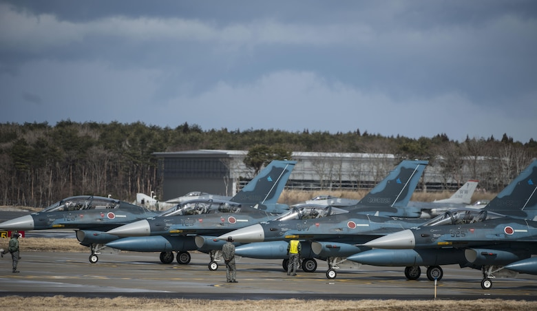 Japan Air Self-Defense Force F-2 Viper Zeros wait on standby as F-16 Fighting Falcons prepare to deploy for a dissimilar air combat-training at Misawa Air Base, Japan, March 17, 2017. The F-16s escorted and cleared the area of enemy ground-to- air missiles and ensured the F-2s were not targeted as they focused on deploying their air-to- ground missiles. (U.S. Air Force photo by Senior Airman Jarrod Vickers)