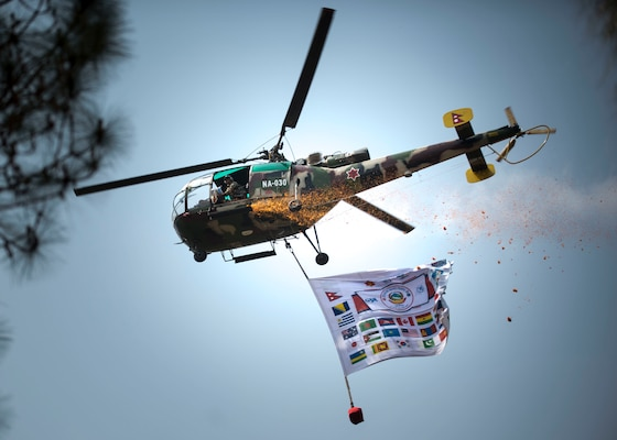 A helicopter does a fly-by dropping flower petals and displaying the banner of all the countries attending exercise Shanti Prayas in Nepal.  Shanti Prayas III is a multinational United Nations peacekeeping exercise designed to provide pre-deployment training to U.N. partner countries in preparation for real-world peacekeeping operations. (U.S. Navy Photo by Petty Officer 2nd Class Taylor Mohr)