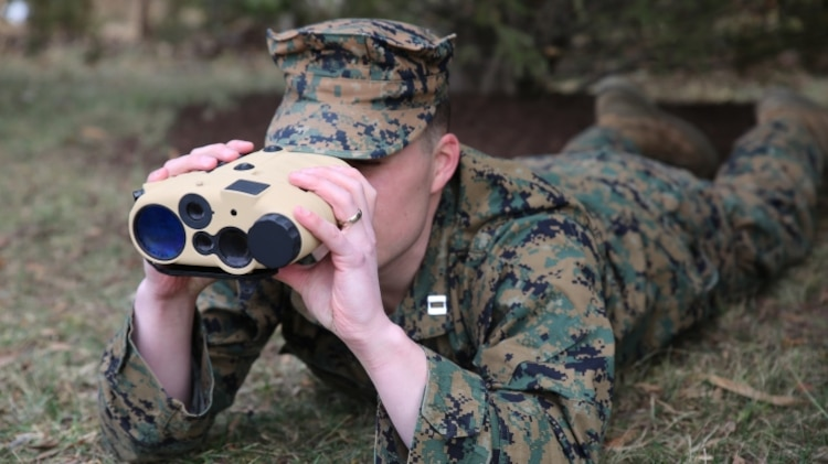 Capt. Patrick Owens, a capabilities integration officer at Marine Corps Combat Development and Integration, demonstrates the Common Laser Range Finder-Integrated Capability system used by dismounted Marines to deliver accurate distance and location of targets through built-in laser range technology. The lightweight, handheld GPS device was fielded in February and replaces the larger, multi-item legacy. Now with just one system, Marines can relay accurate coordinates for lethal, on target fire support. (U.S. Marine Corps photo by Mathuel Browne)
