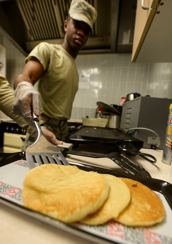 U.S. Air Force Airman 1st Class DeSean Gunter, 100th Communications Squadron client systems technician, prepares pancakes in the base chapel March 21, 2017, on RAF Mildenhall, England. Volunteers and members of the Airmen Committed to Excellence council joined together to make breakfast for junior enlisted personnel across base. (U.S. Air Force photo by Staff Sgt. Micaiah Anthony)
