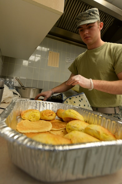 U.S. Air Force Airman 1st Class Austin Gembeck, 100th Maintenance Squadron aerospace ground equipment apprentice, places biscuits in the base chapel March 21, 2017, on RAF Mildenhall, England. Airmen in the ranks from airman basic to senior airman were invited to the base chapel to enjoy a free breakfast, compliments of the Airmen Committed to Excellence council. (U.S. Air Force photo by Staff Sgt. Micaiah Anthony)