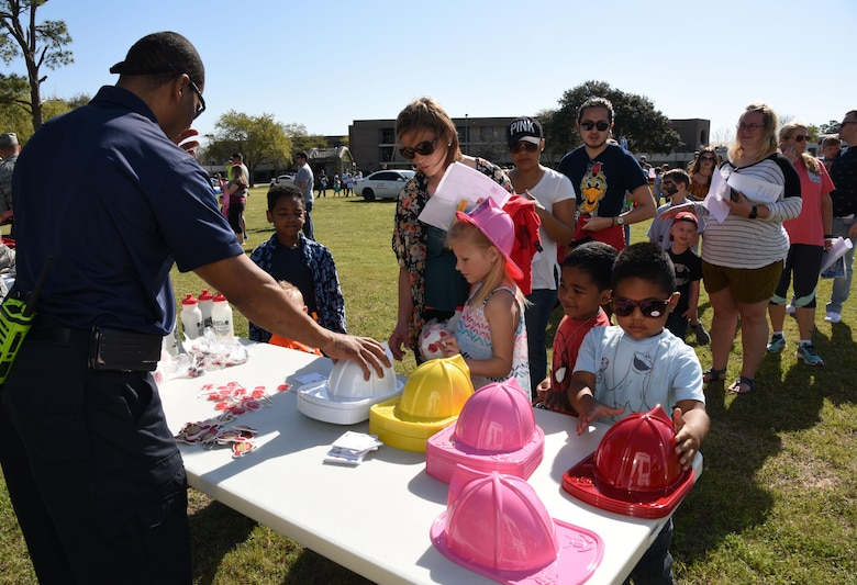 John McIntyre, 81st Infrastructure Division firefighter, provides fire safety instructions and handouts to Keesler families during Operation Hero March 18, 2017, on Keesler Air Force Base, Miss. The activities at the event were designed to help children better understand what their parents do when they deploy. (U.S. Air Force photo by Kemberly Groue)
