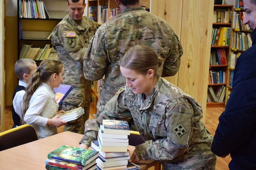 Army Spc. Paige Rayfield, with the 3rd Battalion, 29th Field Artillery Regiment, helps stock new bookcases during a visit to the Mielenku Drawskim Primary School in Drawsko Pomorskie, Poland, March 10, 2017. The battalion's soldiers helped to construct the bookcases for the school during their off-duty hours, continuing a tradition of school volunteerism begun at the unit's home station of Fort Carson, Colo. Army photo by Capt. Brett Tinder