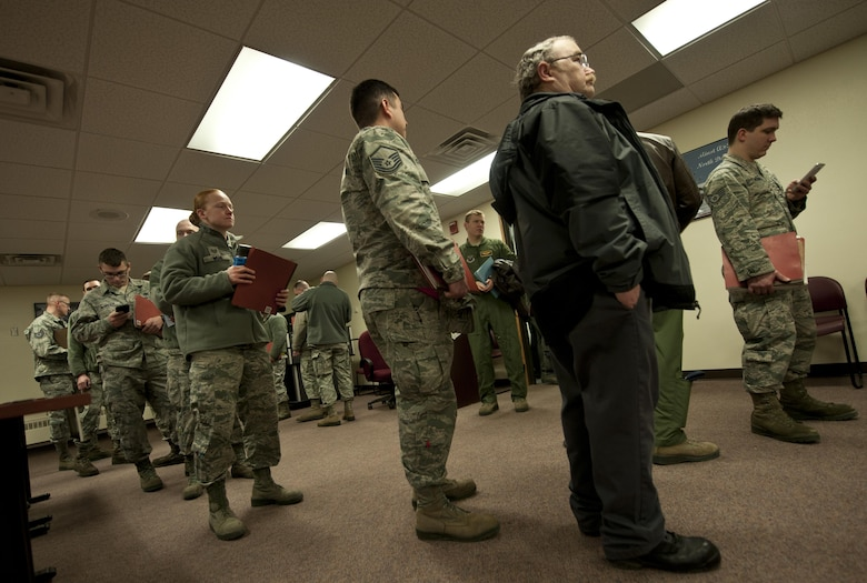 Deployers wait in a personnel deployment function line at Minot Air Force Base, N.D., Feb. 23, 2017. Prior to their departure, each deployer must go through a PDF line, which inspects all of their deployment required paperwork. (U.S. Air Force photo/Airman 1st Class Jonathan McElderry)