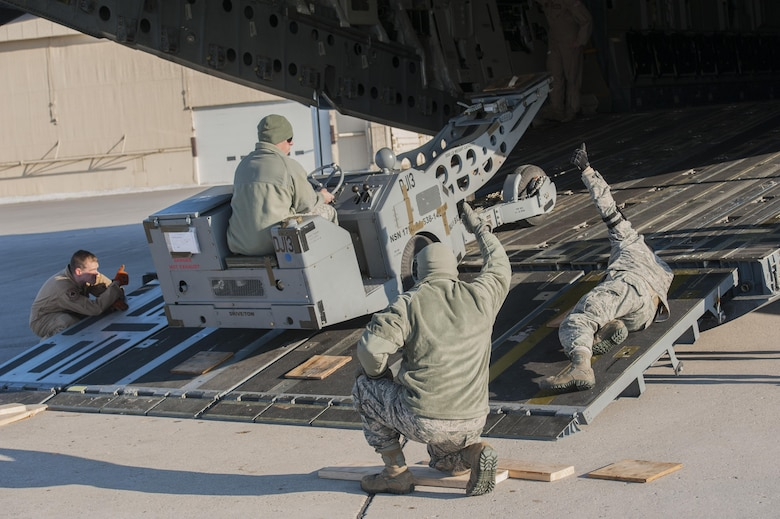 (From left) Staff Sgt. Conor Gillespie, 21st Airlift Squadron loadmaster from Travis Air Force Base, Calif., aids the 5th Logistics Readiness Squadron deployment distributions flight load cargo onto a C-17 Globemaster III at Minot AFB, N.D., March 3, 2017. The mass deployment included more than 400 deployers and 290,000 pounds of cargo. (U.S. Air Force photo/Airman 1st Class Jonathan McElderry)