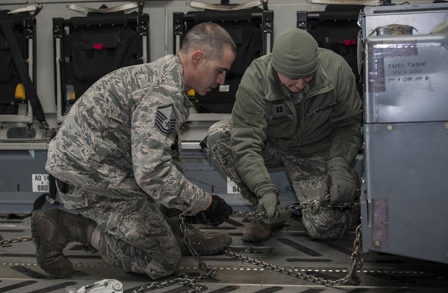 (From left) Master Sgt. Frank Lopez, 5th Logistics Readiness Squadron small air terminal section chief, and Capt. Nicholas Bosch, 5th LRS deployment distributions flight commander, secure cargo onto a C-17 Globemaster III at Minot Air Force Base, N.D., March 3, 2017. The mass deployment included more than 400 deployers and 290,000 pounds of cargo. (U.S. Air Force photo/Airman 1st Class Jonathan McElderry)