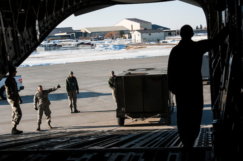 Airmen with the 5th Logistics Readiness Squadron deployment distributions flight load cargo onto a C-17 Globemaster III at Minot Air Force Base, N.D., March 3, 2017. Flight members planned and executed logistics operations, and loaded cargo to support a U.S. Central Command deployment from Minot AFB. (U.S. Air Force photo/Airman 1st Class Jonathan McElderry)