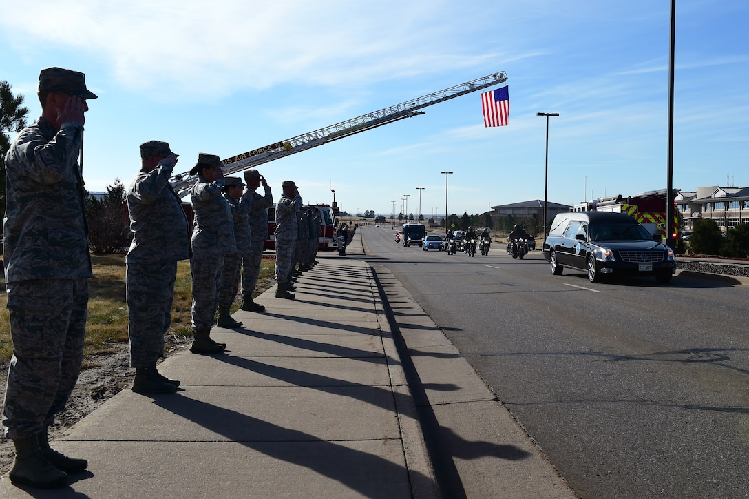 Members of Team Buckley line up to render their final salute to Senior Airman Tien Tran, 566th Intelligence Squadron, March 21, 2017, on Buckley Air Force Base, Colo. Tran was tragically killed in a snowboarding accident earlier this month. The Buckley community paid their respects to Tran and his family at a funeral procession on Aspen Street, from the Mississippi Gate to the 6th Ave. Gate. (U.S. Air Force photo by Airman Jacob Deatherage/Released)