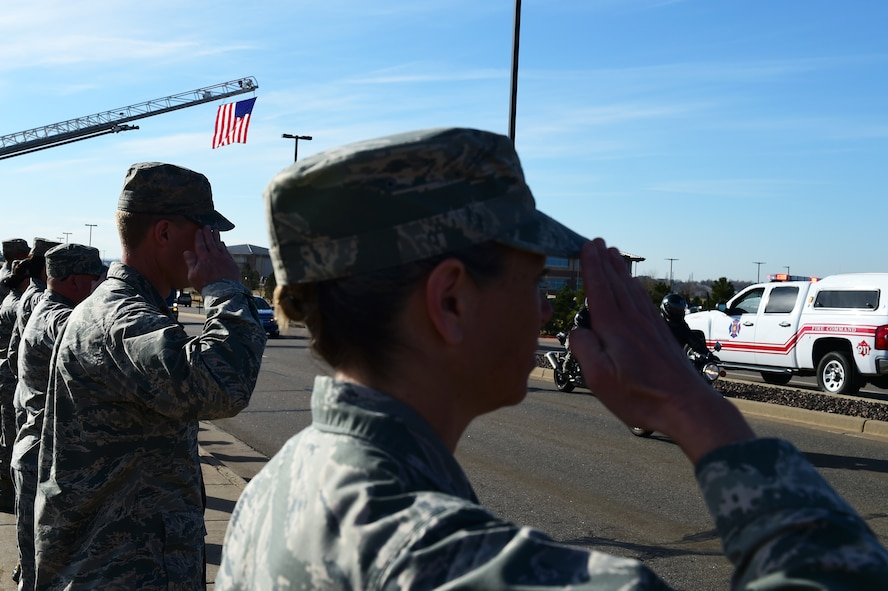 Members of Team Buckley render a final salute to Senior Airmen Tien Tran, 566th Intelligence Squadron, March 21, 2017, on Buckley Air Force Base, Colo. The funeral procession took place along Aspen Street, from the Mississippi Gate to the 6th Ave. Gate. He was transferred from the Denver International Airport to Hilo, Hawaii, for his internment March 24. (U.S. Air Force photo by Airman Jacob Deatherage/Released)