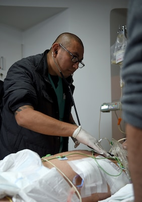 U.S. Army Capt. Sabas Salgado, an Army Institute of Surgical Research nurse, listens to a patient's lung sounds in a hospital in South America Feb. 16, 2017. Salgado was part of the medical team that transported a patient from South America to the San Antonio Military Medical Center in Texas for further treatment. (U.S. Air Force photo/Staff Sgt. Jerilyn Quintanilla)