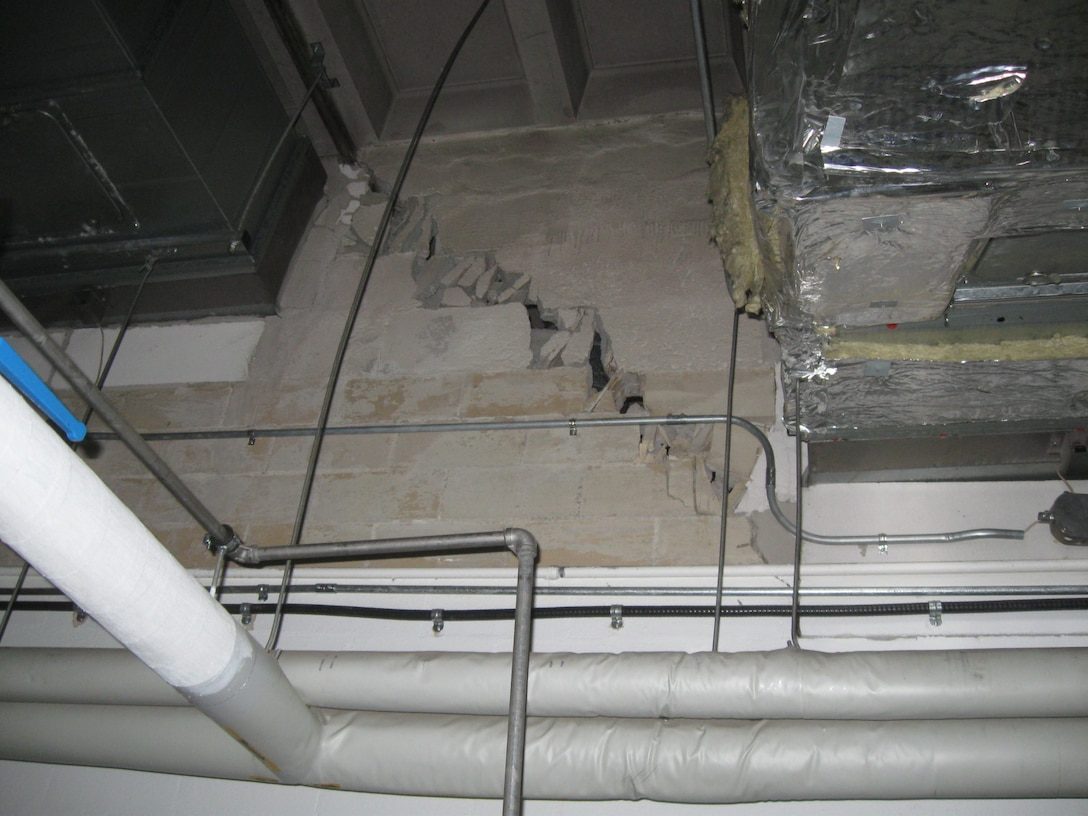 A large crack in the structure's wall shows the effects of permafrost thaw on the building's foundation.