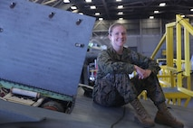 Cpl. Callahan Brown sits atop an aircraft that's undergoing maintenance at Marine Aviation Logistics Squadron 26 on Marine Corps Air Station New River, Mar 3. Brown is currently a full time student at Coastal Carolina Community College and plans to commission to become an officer when she becomes a sergeant or completes her degree. Brown is the adjutant for MALS 26. (U.S. Marine Corps photo by Lance Cpl. Juan Madrigal)