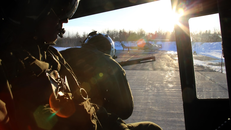 Sgt. Ty Morgan (left) and Cpl. Landon Cheek (center) keep watch out the back of a UH-1Y Venom as it takes off to conduct night-time cold weather operations aboard Fort Drum, N.Y., March 17, 2017. Marines assigned to Marine Light Attack Helicopter Squadron 269, Marine Aircraft Group 29, 2nd Marine Aircraft Wing, conducted close air support at night with live ordnance to simulate real world operations in a forward position. Morgan and Cheek are crew chiefs with HMLA-269. (U.S. Marine Corps photo by Cpl. Mackenzie Gibson/Released)