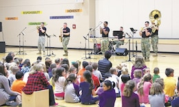 "The ""Big Red One"" Brass Band plays for a gymnasium full of students from USD 346 at Jayhawk Elementary School, Mound City, Kansas, March 7. The band played as part of the Music In Our Schools celebration held during the month of March."