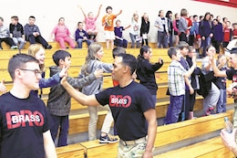 "Members of the ""Big Red One"" Brass Band exchange high fives with students following a concert at Jayhawk Elementary School, Mound City, Kansas, March 7."