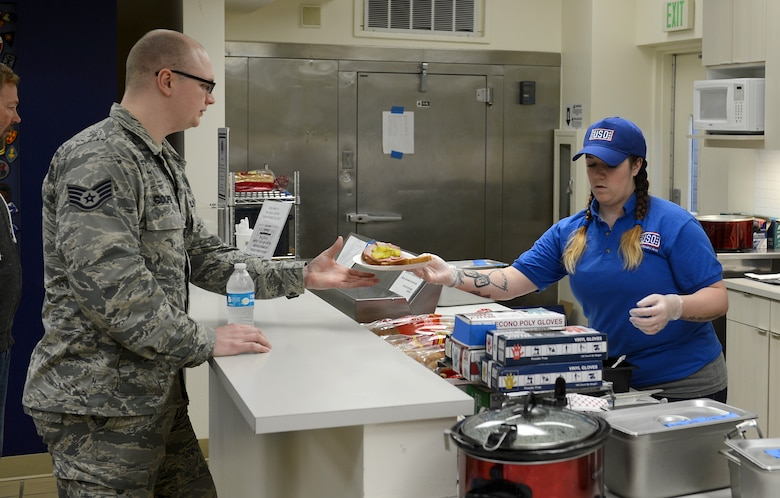 Kate Jones, United Service Organizations Northwest Shali Center volunteer, serves lunch to Staff Sgt. Evan Cooper, 446th Aeromedical Staging Squadron medical technician, Mar. 21, 2017 at Joint Base Lewis-McChord, Wash. The Shali Center and its staff of volunteers stay busy throughout the year serving more than 48,000 troops annually. (U.S. Air Force/Senior Airman Divine Cox)