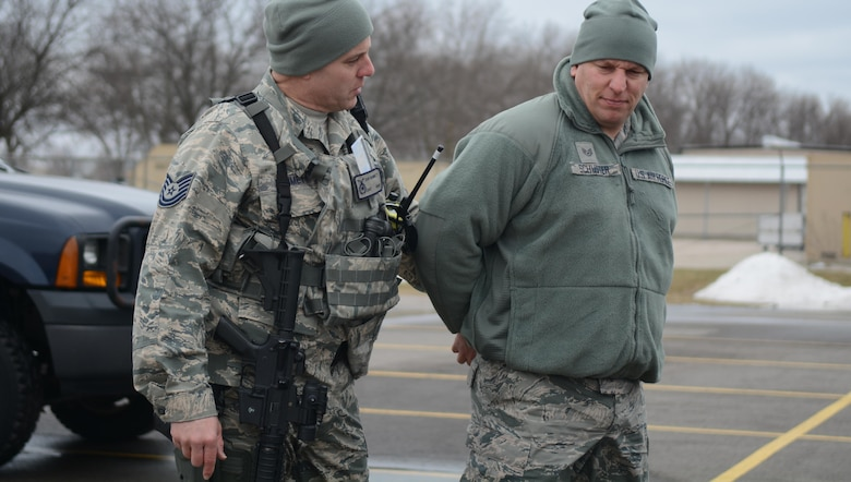 Tech. Sgt. Dan Hammett, 115th Fighter Wing Security Forces Squadron fire team leader, handcuffs and questions Staff Sgt. Christopher Schuster, 115 FW SFS Airman, during the squadron's quarterly capstone exercise on base March 18, 2017. The capstone exercise gave security forces Airmen a chance to train on law enforcement fundamentals, knowledge they need when deployed with active duty units. The training gave drill status guardsmen and the full-time active guard reserve Airmen a chance to work together. (U.S. Air National Guard photo by Staff Sgt. Andrea F. Rhode/released)