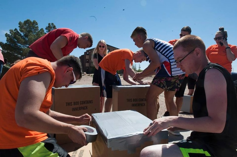 Airmen use cardboard and duct tape to create a boat during the 49th Wing Sports Day, March 17, 2017 at Holloman Air Force Base, N.M. Once completed, Airmen took their boats to the pool for a cardboard boat race. (U.S. Air Force photo by Airman 1st Class Ilyana Escalona)