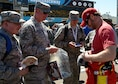 Dale Earnhardt Jr., NASCAR driver, autographs merchandise for Airmen during the introduction of the racers at the Camping World 500 Mar. 19, 2017, at the Phoenix International Raceway, Avondale, Ariz. (U.S. Air Force photo by Airman First Class Alexander Cook)