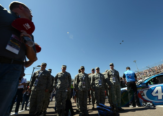 Airmen from Luke Air Force Base stand at attention while two F-35s from the 62nd Fighter Squadron perform a flyover during the opening ceremony of the Camping World 500 Mar. 19, 2017, at the Phoenix International Raceway, Avondale, Ariz. (U.S. Air Force photo by Airman First Class Alexander Cook)