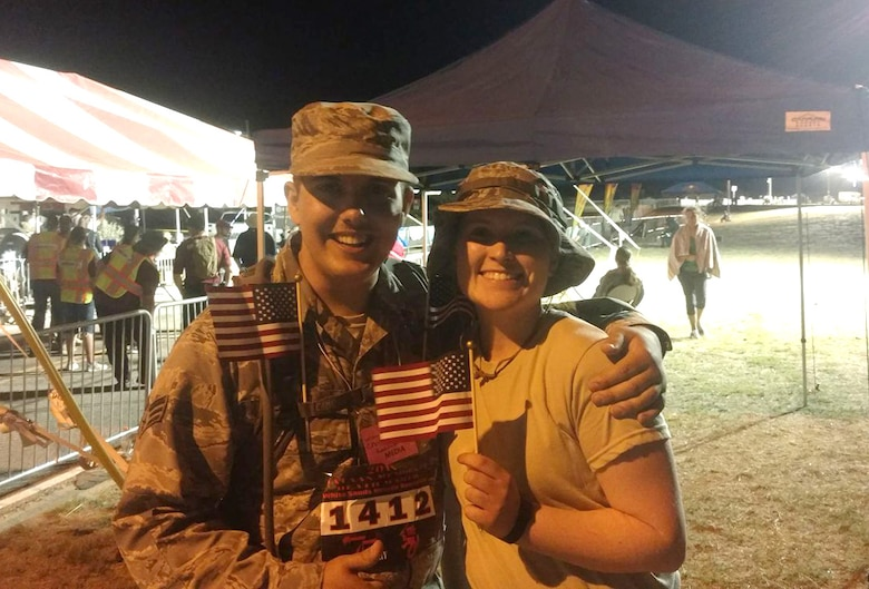 Senior Airman Chandler Baker and Airman Lexi Crawford, 377th Air Base Wing's Public Affairs Office, celebrate successfully completing the Bataan Memorial Death March to pose for a photo. The two participated in a 26-mile march through the high desert terrain of the White Sands Missile Range, N.M. The memorial march is conducted in honor of the heroic service members who defended the Philippine Islands during World War II, sacrificing their freedom, health, and, in many cases, their very lives. (Courtesy Photo)