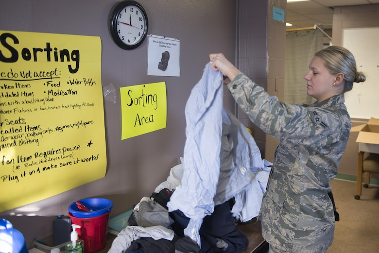 U.S. Air Force Airman 1st Class Angela White, a 354th Force Support Squadron military personnel section customer service apprentice, sorts through donated clothing March 16, 2017, at Eielson Air Force Base, Alaska. White volunteers at the Airman's Attic as often as possible to ensure the facility can remain open to her fellow Airmen. (U.S. Air Force photo by Airman Eric M. Fisher)