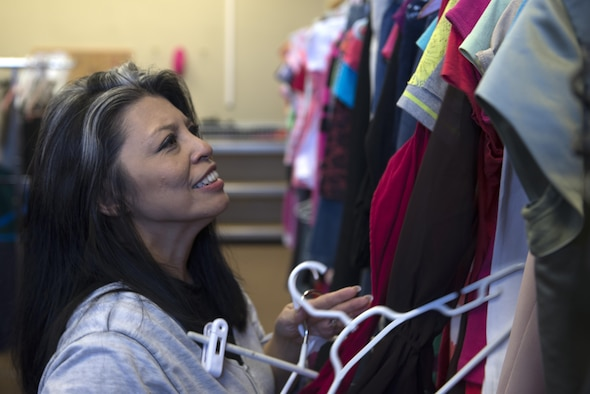 Bobbie Candaso, the Eielson Airman's Attic lead volunteer, hangs clothing March 16, 2017, at Eielson Air Force Base, Alaska. Once items are checked for defects, they're categorized and displayed throughout the Airman's Attic so customers can easily find what they need. (U.S. Air Force photo by Airman Eric M. Fisher)