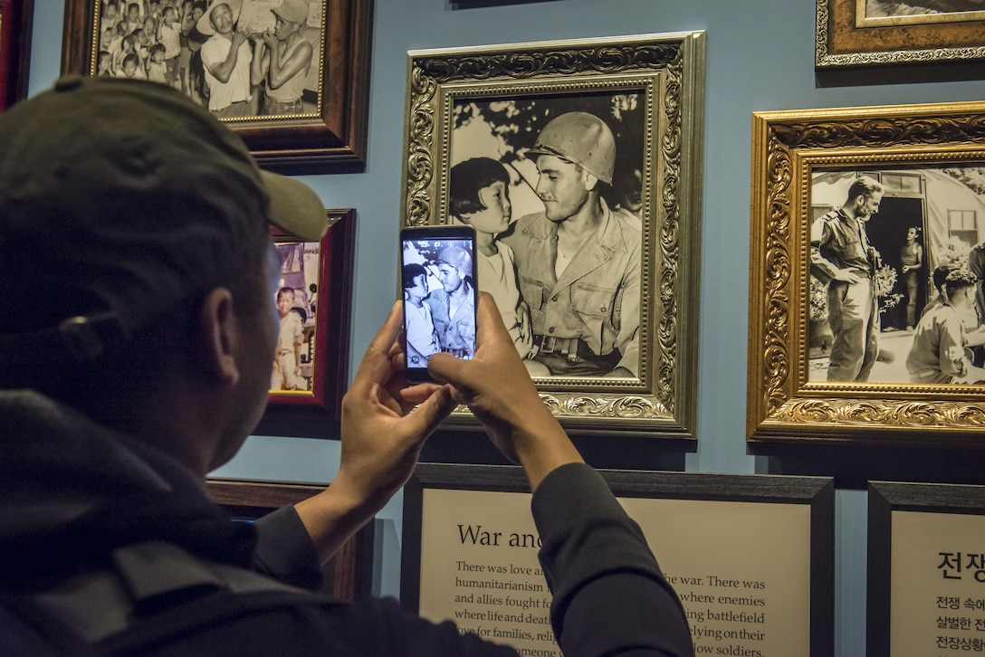 """U.S. Air Force Tech. Sgt. Malo Jones , an administration craftsman home stationed at  Headquarters Air Force at the Pentagon in the District of Columbia, snaps a photo with his smartphone of a U.S. soldier and a North Korean girl framed in time by the black and white portrait from the Korean War at the War Memorial of Korea in Seoul, Republic of Korea, March 18, 2017. A plaque just below this photo entitled, """"War and Love,"""" reads, """"There was love among soldiers even in the war. There was humanitarianism in the bloody battlefield where enemies and allies fought for their lives. In the terrifying battlefield where life and death intersected, they fought relying on their love for families, religious beliefs and trust of fellow soldiers. And when someone was injured, regardless of whether the person was friend or foe, as human beings they took care of the person. (U.S. Air Force photo by Staff Sgt. Benjamin W. Stratton)"""