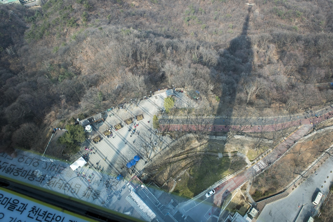 At 1,575 feet above sea level, the Namsan Seoul Tower is the first tower-type tourism spot in Korea with views as far as the eye can see and pictured here its shadow extends well beyond the base into the surrounding park and forest in Seoul, Republic of Korea, March 18, 2017. A group of 60 U.S. service members assigned to Key Resolve 2017 hiked the steep hill hoping to get a glimpse of the ROK's capital on a first-ever tour to Seoul where they experienced the Korean culture first-hand. The tower is Korea's first general radio wave tower. It was built to promote the future of broadcasting and the tourism industry. It combines a broadcast tower and an observatory which embodies traditional Korean design. (U.S. Air Force photo by Staff Sgt. Benjamin W. Stratton)