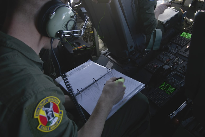 Staff Sgt. Christopher Hofer, 36th Airlift Squadron loadmaster, fills out a flight record form during the first Yokota C-130J Super Hercules training sortie over the skies of Japan March 20, 2017. The form allows the aircrew to document any discrepancies discovered by themselves or maintenance personnel. (U.S. Air Force photo by Staff Sgt. David Owsianka)