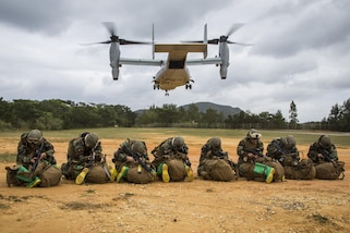 Marines assigned to the 3rd Marine Division's Chemical, Biological, Radiological and Nuclear Platoon protect themselves from debris as an MV-22 Osprey lands at Landing Zone Dodo, Camp Hansen, Okinawa, Japan, March 21, 2017. Marine Corps photo by Lance Cpl. Jesus McCloud