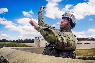 A soldier throws a live M67 fragmentation hand grenade during a training event at Fort Bragg, N.C., March 19, 2017. The soldier is assigned to the 122nd Aviation Support Battalion. Army photo by Sgt. Steven Galimore