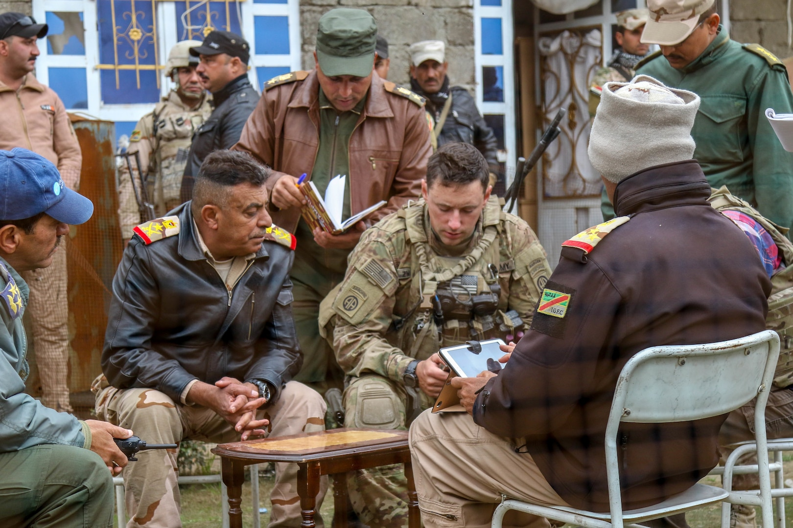 U.S. Army Capt. Mark G. Zwirgzdas, deployed in support of Combined Joint Task Force-Operation Inherent Resolve, assigned to 2nd Brigade Combat Team, 82nd Airborne Division, discusses operations during the offensive to liberate West Mosul from ISIS with 9th Iraqi Army Division leaders near Al Tarab, Iraq, March 19, 2017. The 2nd BCT, 82nd Abn, Div., enables their Iraqi security forces partners through the advise and assist mission, contributing planning, intelligence collection and analysis, force protection, and precision fires to achieve the military defeat of ISIS. CJTF-OIR is the global Coalition to defeat ISIS in Iraq and Syria. (U.S. Army photo by Staff Sgt. Jason Hull)
