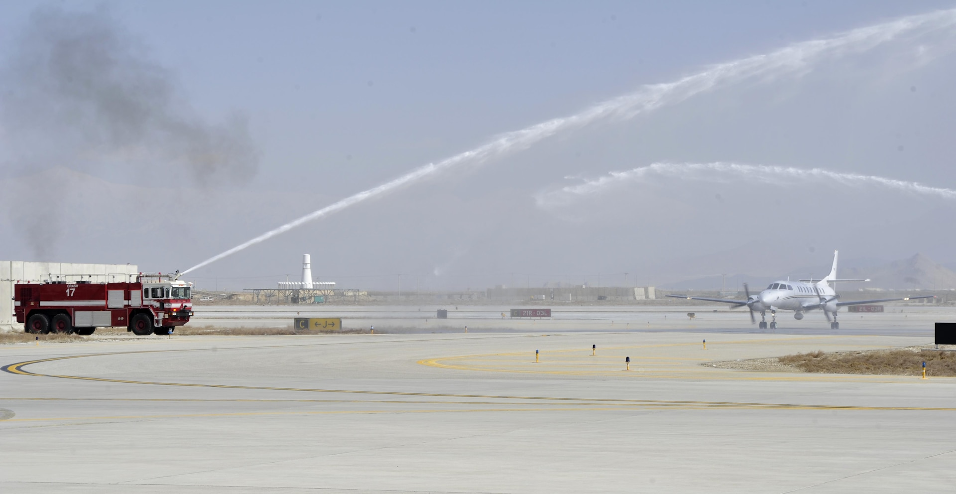 BAGRAM AIRFIELD, Afghanistan (Mar. 17, 2017) - Water plumes greet and honor the final flight of Chief Warrant Officer 4 Joshua Wade Martin as he taxis his C-26 Metroliner to the ramp.  Martin is a 28-year Arkansas Army National Guard veteran who will redeploy soon and retire from military service this summer.  The water salute is an aviation tradition to celebrate a momentous occasion in aviation history.  Photo by Bob Harrison, U.S. Forces Afghanistan Public Affairs.