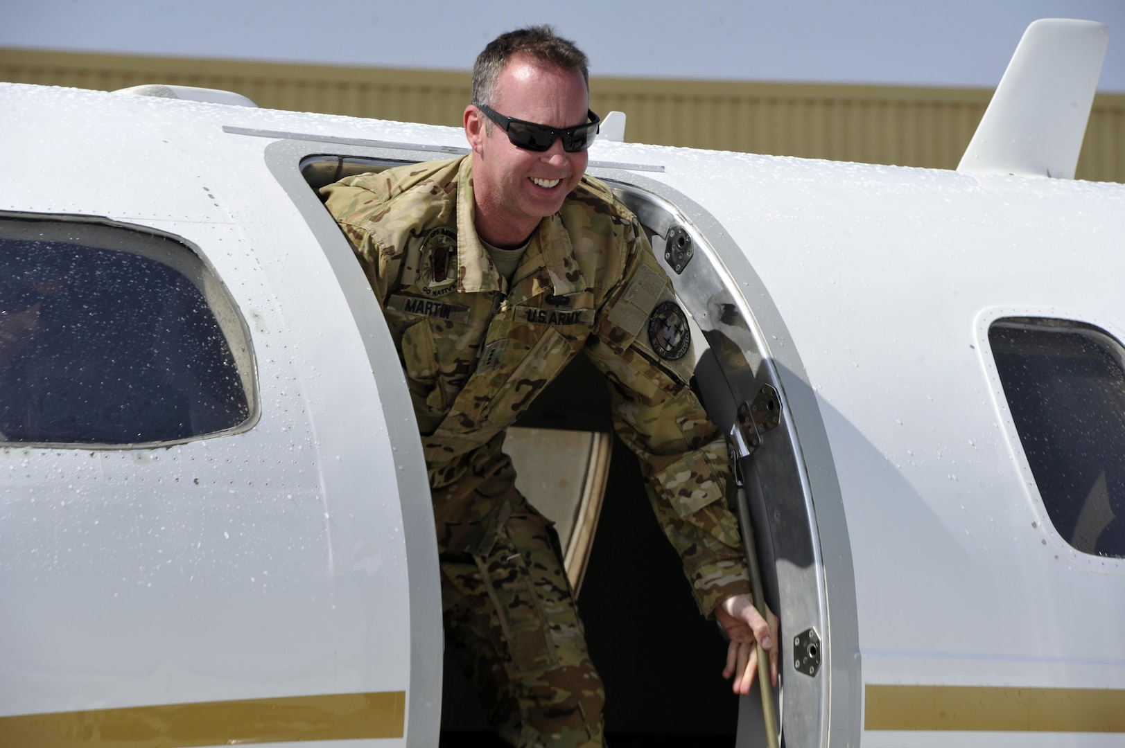 BAGRAM AIRFIELD, Afghanistan (Mar. 17, 2017) - Chief Warrant Officer 4 Joshua Wade Martin exits his C-26 Metrolina aircraft moments after landing here for his final military flight.  Martin is a 28-year veteran of the Arkansas Army National Guard who will redeploy soon and retire from military service this summer.  His team greeted his arrival for his last military flight with the traditional aviation water salute.  Photo by Bob Harrison, U.S. Forces Afghanistan Public Affairs.