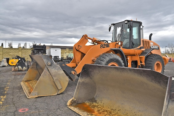 """Airman 1st Class Manuel Rivera Matos, 92nd Civil Engineer Squadron pavement and construction journeyman, prepares the loader by switching out attachments Mar. 15, 2017, at Fairchild Air Force Base, Washington. The 92nd CES pavement and construction Airmen and civilians, often referred to as """"Dirt Boyz,"""" were recently named the winners of the American Association of Airport Executives' Balchen/Post Award for their outstanding performance in snow removal during the 2016 season. (U.S. Air Force photo/Senior Airman Mackenzie Richardson)"""