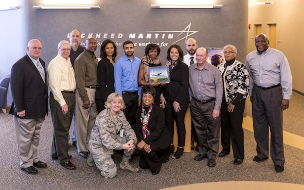 Anthony Zompetti, the Air Force's director of Development & Production, C-130 Hercules Division, presented the Defense Contract Management Agency Lockheed Martin Marietta team with a token of appreciation in February for saving the government $680 million on its $5.3 billion contract for C-130 Hercules aircraft. Zompetti stands with DCMA employees Barry Lubrant, David Wolfinge, Richard Bolden, Priscilla Driscoll, Miral Patel, Marguerite Antoine, Sarah Sullivan, Isaiah Wilcox, Phillip Beckwith, LaNorma Shelton-Thomas and Bernard Latimore. Kneeling are Air Force Col. Sheri Bennington, DCMA Lockheed Martin Marietta commander, and Myra Tate, deputy commander. Team members Todd Landeche, Marieco Myart, Dexter Harper, Rachel Buckner and Rocky Miller are not shown. (DCMA photo courtesy of DCMA Lockheed Martin Marietta)