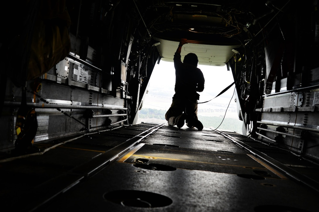 A flight engineer assigned to the 7th Special Operations Squadron opens the cargo ramp of a CV-22 Osprey assigned to the 7th Special Operations Squadron, March 17, 2017, over RAF Mildenhall, England. Once the aircraft neared the drop zone, members of the 321st Special Tactics Squadron prepared for a military free fall. The exercise allows flight crew and 321st STS Air Commandos to practice safely deploying from aircraft to reach designated drop zones. (U.S. Air Force photo by Senior Airman Justine Rho)