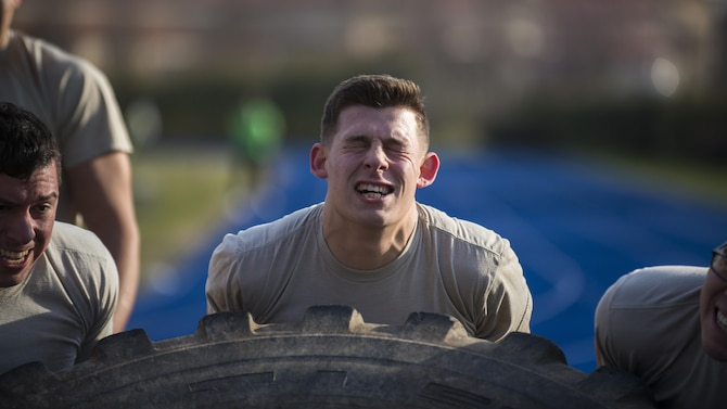 Airman 1st Class Nicholas Castellucci, 724th Air Mobility Squadron member, flips a tire with his teammates during the first Combat Warrior Challenge at Aviano Air Base, March 14, 2017. The four-day competition included obstacles such as a wall climb, tire flip, and kettle bell carry. (U.S. Air Force photo by Senior Airman Cory W. Bush)