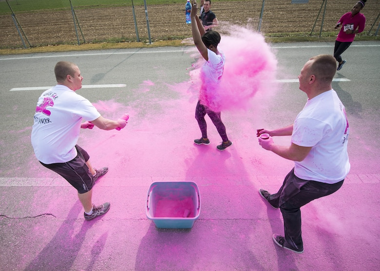 A Team Aviano member runs through pink powder during the 11th Annual Breast Cancer Awareness Walk at Aviano Air Base, Italy, March 18, 2017. The event had its largest turnout and money raised since its inception. (U.S. Air Force photo by Senior Airman Cory W. Bush)