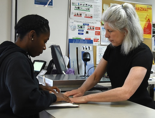 Sharon McCrea, Malmstrom Air Force Base postmaster, right, helps 2nd Lt. Eboni Simpson, 12th Missile Squadron missileer, tape down a package prior to mailing it off at the base contract postal unit March 21, 2017, at Malmstrom Air Force Base, Mont. Daily, the base post office sends out approximately 300 pounds of mail to different locations. (U.S. Air Force photo/Senior Airman Jaeda Tookes)